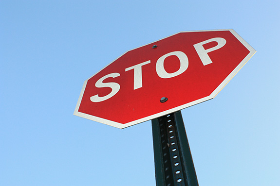 A red stop sign is seen from below.